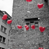 Heart shaped balloons float through the air.