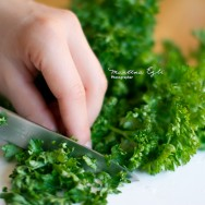 Person cutting Parsley on a chopping board
