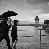 Two people walk with an umbrella past the old bridge in Luzern, Switzerland