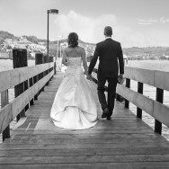 Newly wed&#039;s walk along a pier.