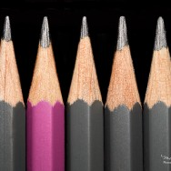 A pink pencil surrounded by grey pencils