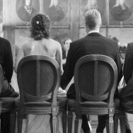 A seated couple undertaking their nuptuals, photographed from behind.