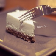 A slice of New York Cheesecake and a fork.
