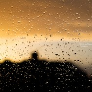A sunset seen through a window full of raindrops.