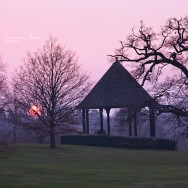 The setting sun and a silhouette of a pavilion.
