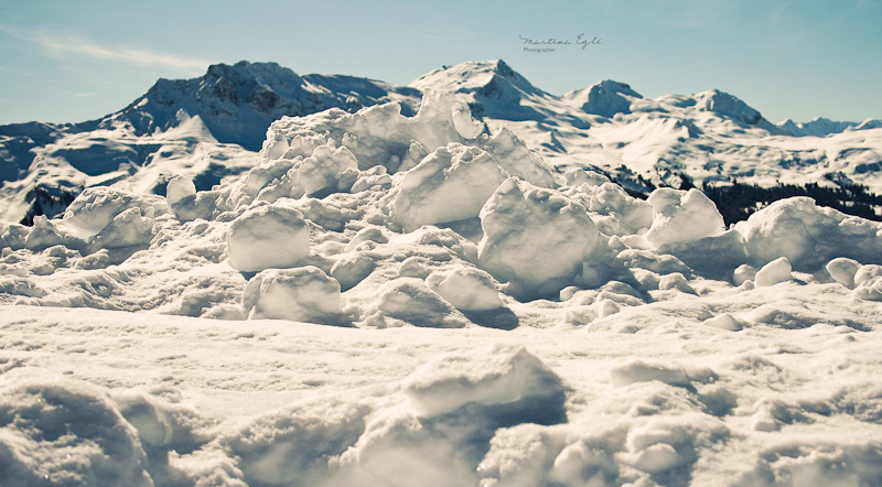 A pile of snow with the Alps in the background.