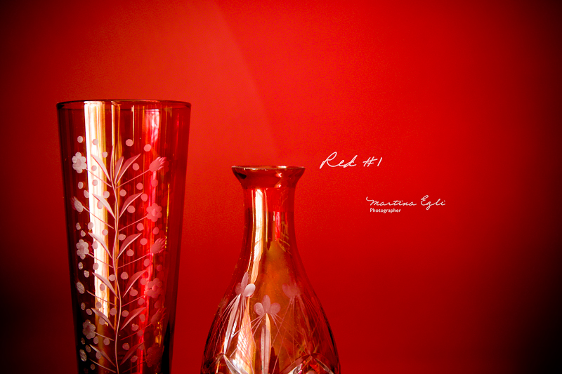 A red vase and a red bottle against a red wall.