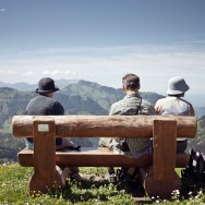 A group of people sit on a bench overlooking the Swiss Alps.