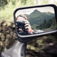 A self portrait reflected in a car wing mirror, a moutain in the background.