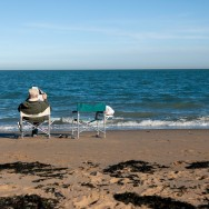 An elderly man is sitting in a seat at the beach while reading the newspaper, there is an empty seat next to him.