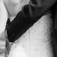 Bride and groom stand arm in arm.