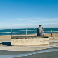 A man sits near a beach and watches ships go sailing by.