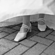 A bride lifts her dress to reveal her wedding shoes.