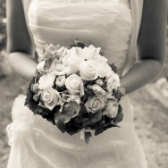 A wonderful bride is holding her beautiful bridal bouquet made from white roses.