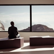 A man looks out upon the Swiss alps from the peak of mount Pilatus.
