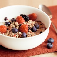 A tasty muesli with raspberries, blueberries and blackberries in a white bowl.