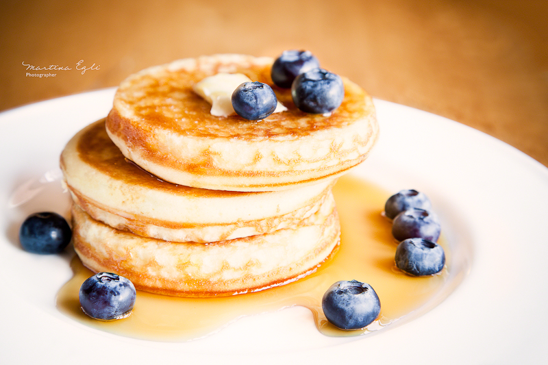 American pancakes with maple syrup and bluerberries on a white plate.