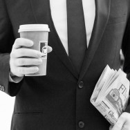 A b&amp;w image of a man in a suit holding a coffee to go and the financial times.