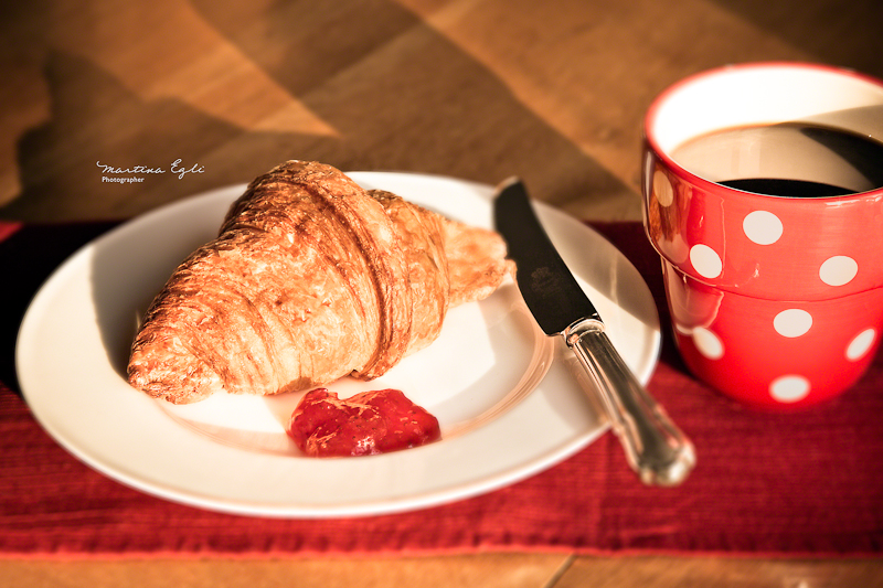 A croissant and some jam on a white plate with a cup of black coffee.