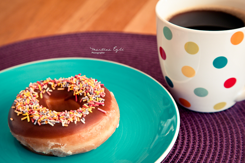 A cup of coffee and a doughnut.