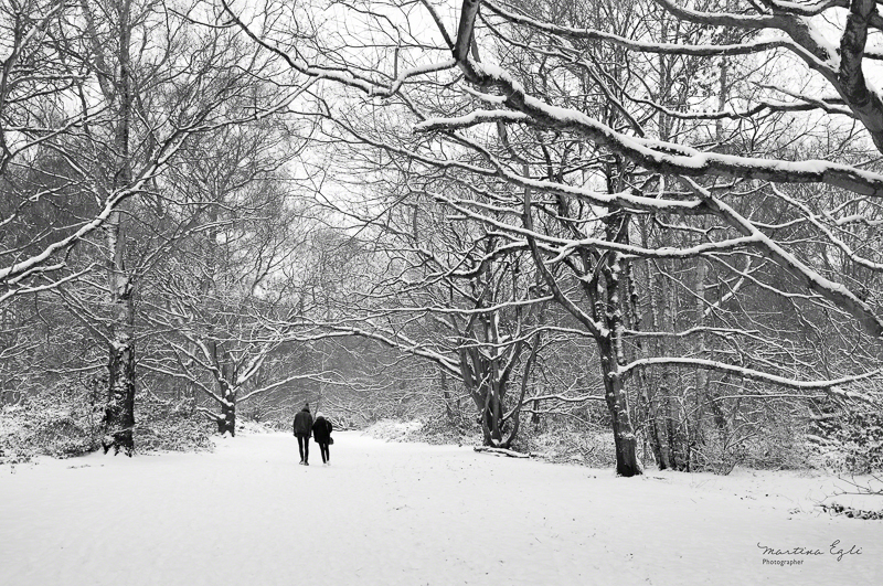 A couple walk in the snow.