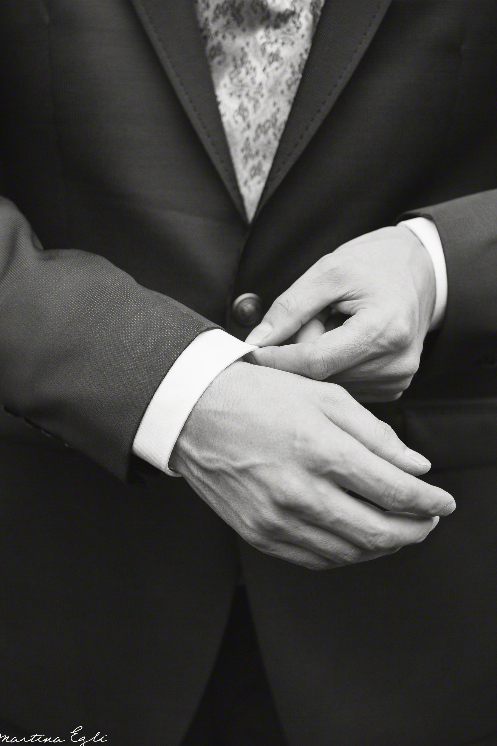 A Groom adjust his cuffs.