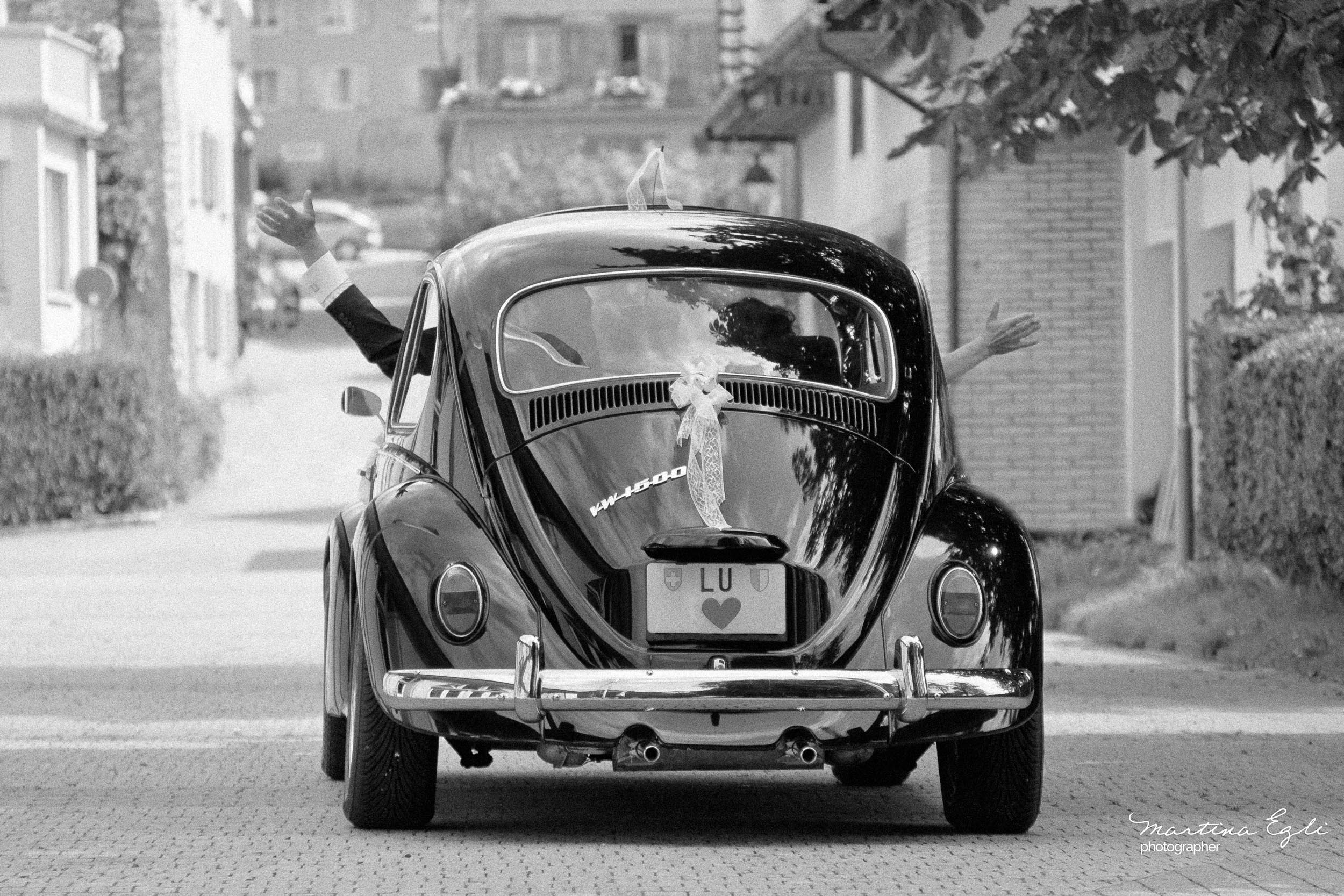 The Bride and Groom depart in their love-bug