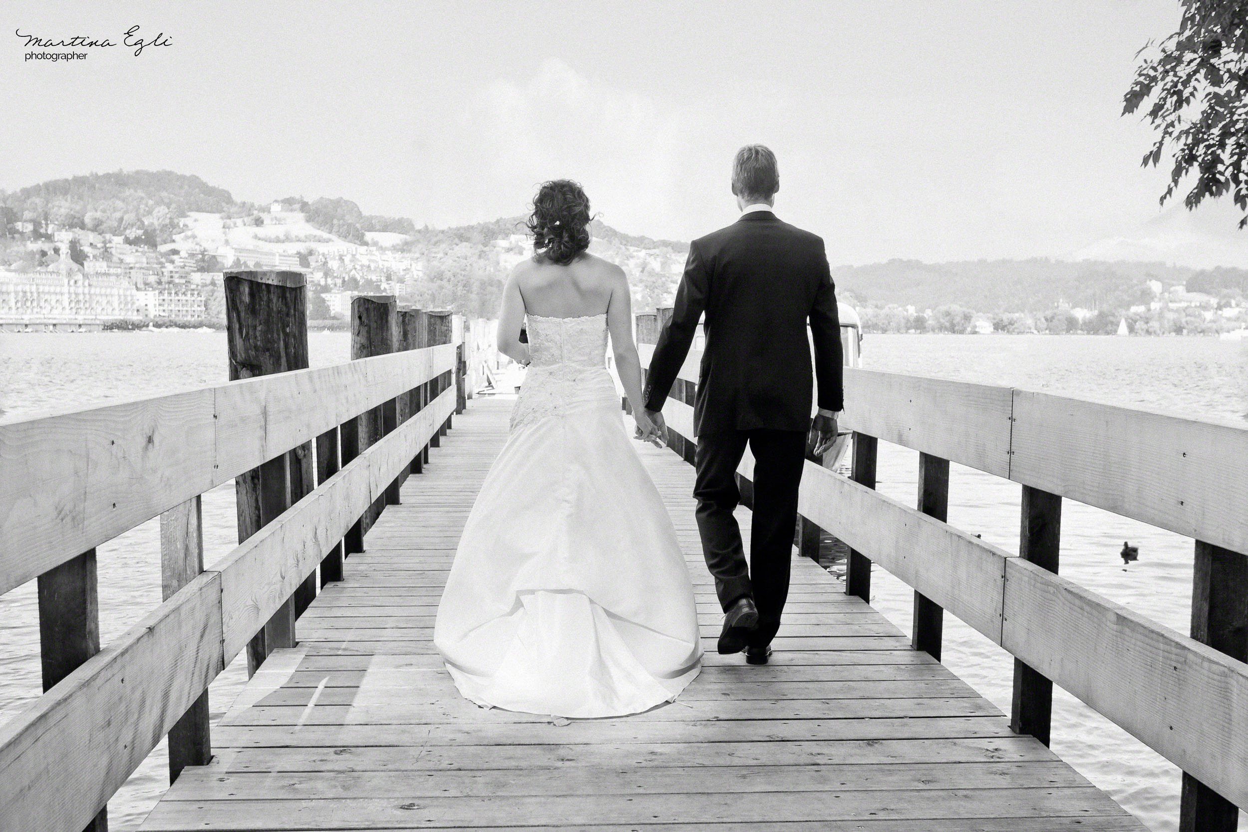 A Bride and Groom walk along a pier