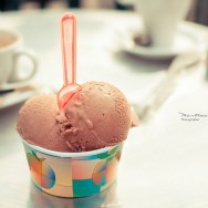 A tub of chocolate ice cream and pink spoon.