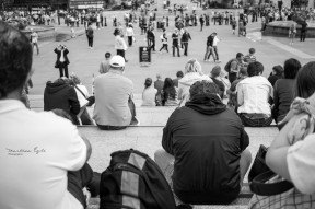 People sitting on the steps of Trafalgar Square in London.