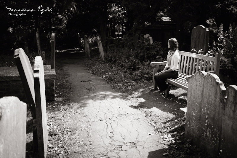 A young woman sits alone in a graveyard.