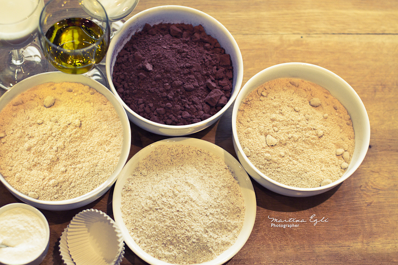 Four bowls full of flour, ground hazelnuts, sugar and cacao powder.