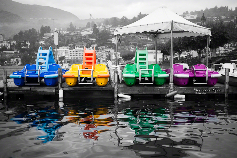 Four pedalos on a lake.