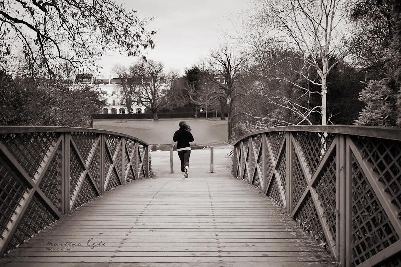 A jogger crossing a bridge.