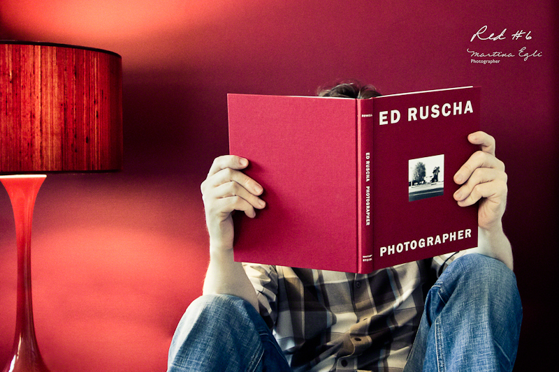 A man is reading a red book in front of a red wall and next to a red lamp.