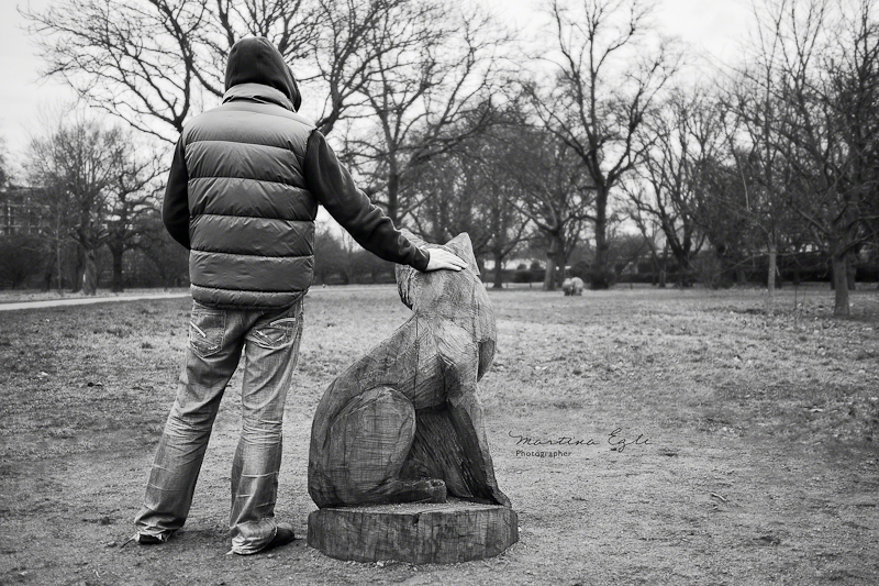 A man with sculpture of a wolf in Regents Park, London.