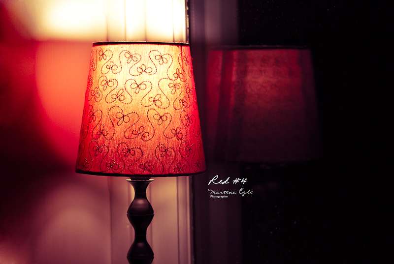 A red table lamp and its reflection in the window.