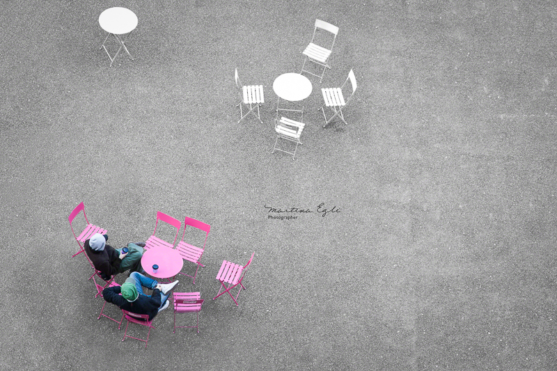 Two men drinking coffee at a pink table taken from a vantage point.