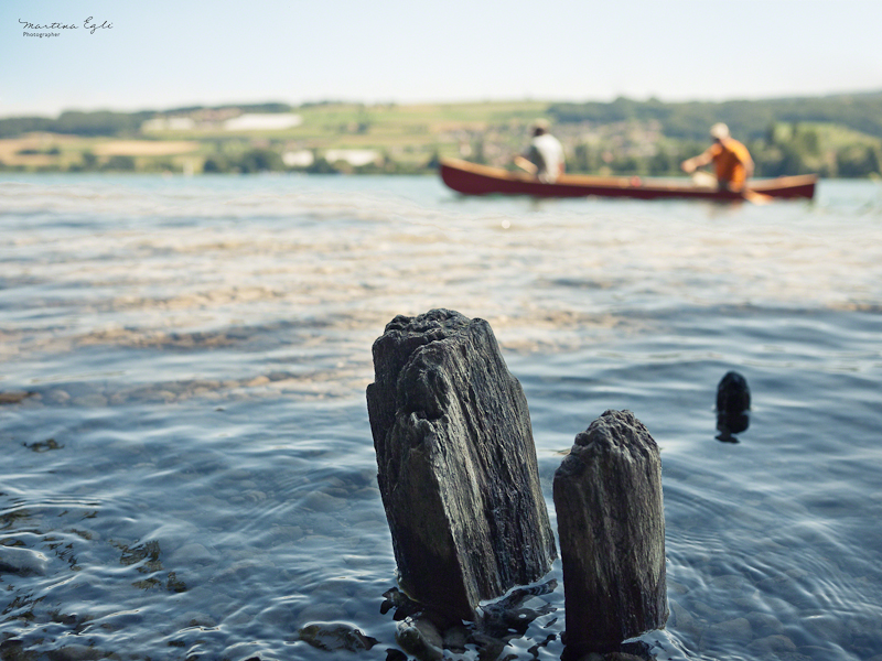Canoeists glide into the frame of a landscape.