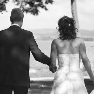 Newlyweds walk hand in hand towards a lake