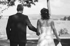Newlyweds walk hand in hand towards a lake