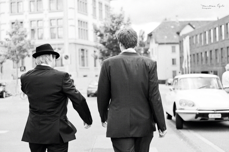 The groom and best man walk down the street.