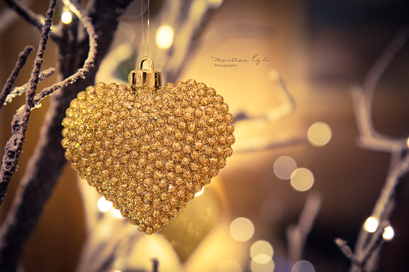 A golden heart hanging on a tree as a Christmas decoration.