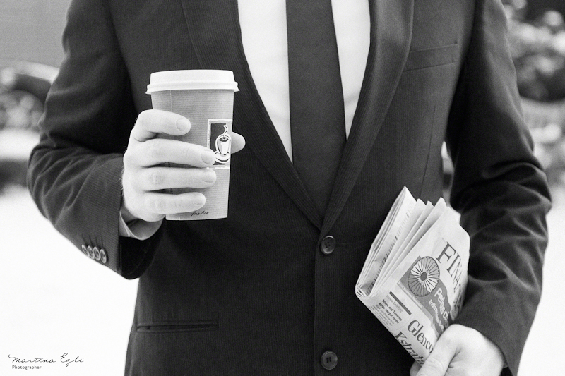 A b&w image of a man in a suit holding a coffee to go and the financial times.