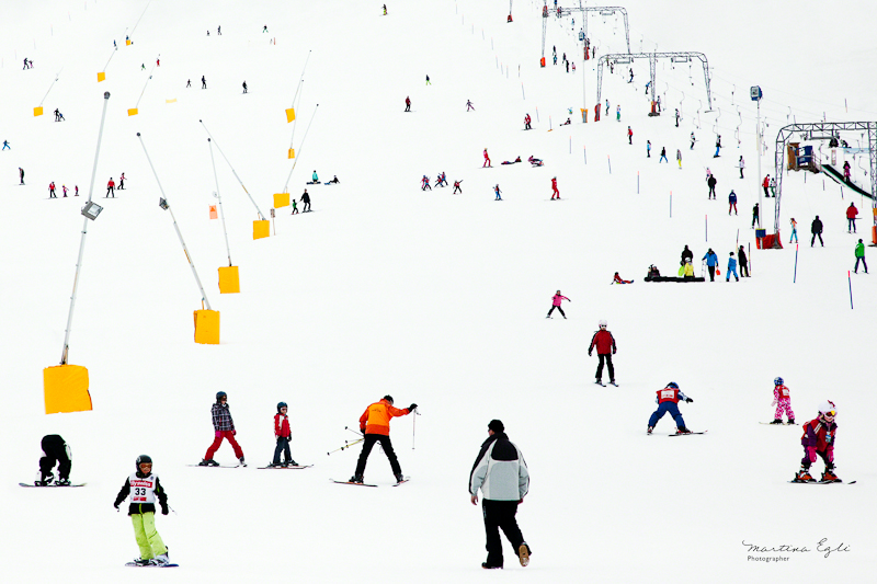 A ski slope in Switzerland full of skiers and snowboarders in colourful clothes.