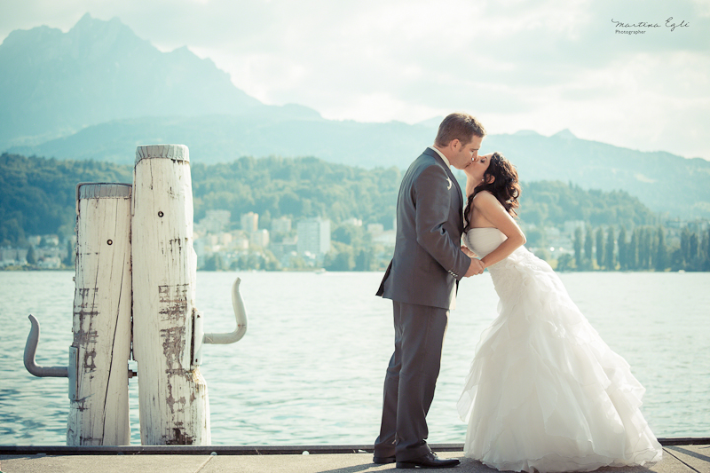 A Bride and Groom kiss on a waterfront pier