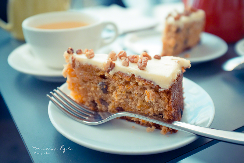 A carrot cake on a white plate with a cup of tea.